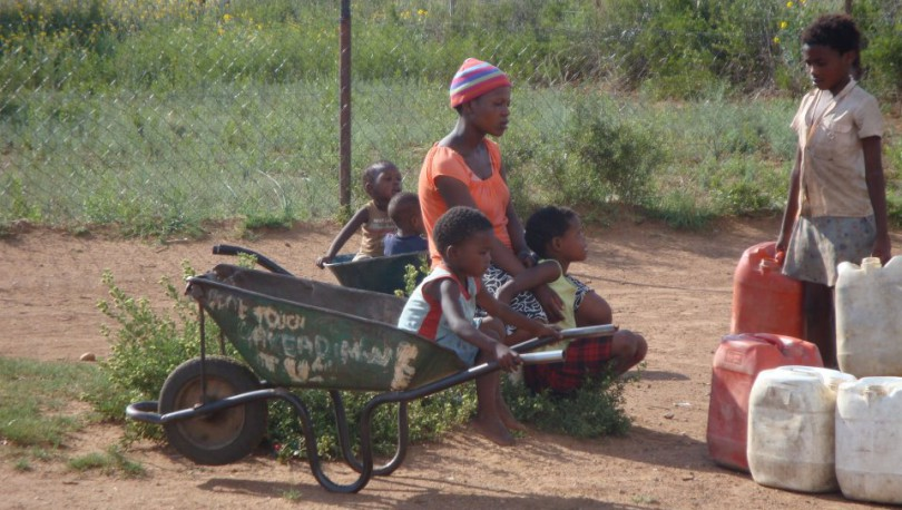 Children in Rooigrond with wheel barrows to carry water containers