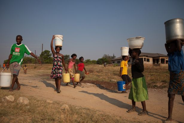 Women in Lusaka township carrying water containers