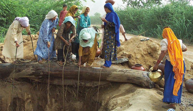 Women draw water at a water hole in India